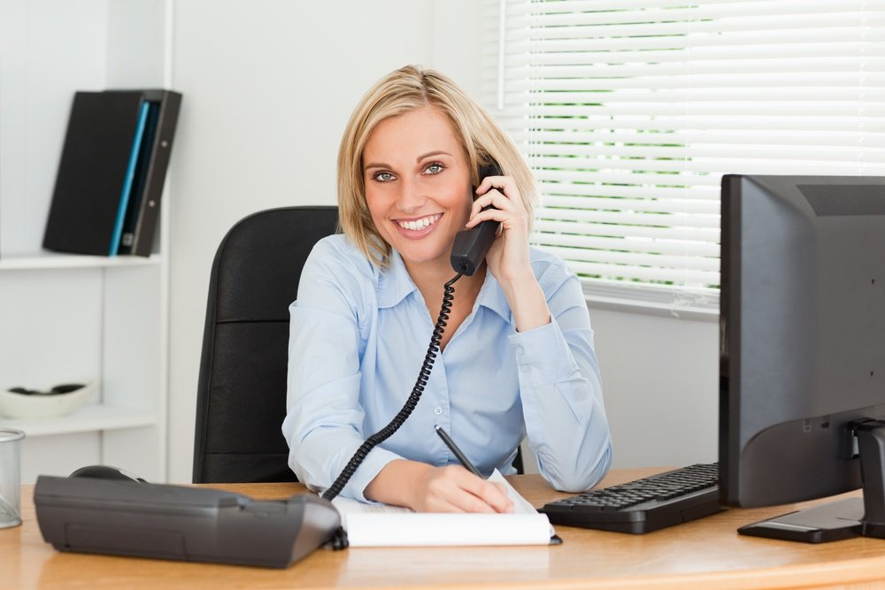 Cute businesswoman on phone writing something down looks into camera in her office.jpeg